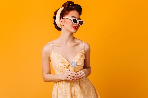 サングラスでポーズをとる愛らしいピンナップ女性。黄色の空間に分離されたロリポップと生姜の女の子のスタジオショット。