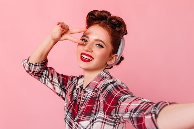 セルフィーを作る明るいメイクで愛らしいピンナップ女性。ピースサインを示す市松模様のシャツを着た魅力的な女の子のスタジオショット。