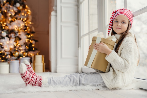 Adorable pleasant looking girl wears comfortable warm clothes, holds wrapped gift box