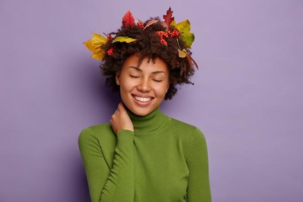 Adorabile donna dalla pelle scura soddisfatta prova felicità e gioia, tocca il collo, indossa un maglione verde, posa al coperto