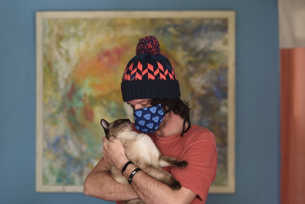 Adorable portrait of creative man with face mask loving his feline pet.