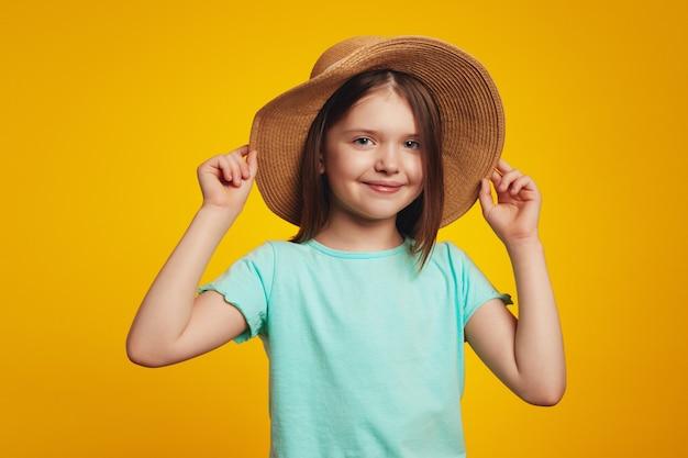Очаровательная позитивная активная девочка в синей футболке и стильной шляпе