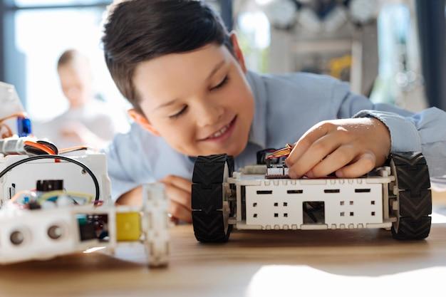 Очаровательные дети предподросткового возраста осматривают мастерскую роботизированных транспортных средств Premium Фотографии