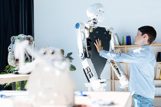 Очаровательные дети предподросткового возраста осматривают мастерскую роботизированных транспортных средств