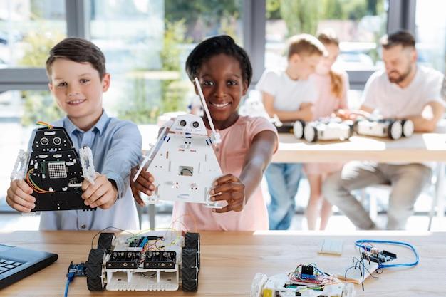 로봇 차량 작업장을 검사하는 사랑스러운 십대 전 아이들