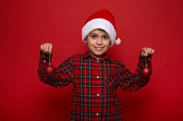 Очаровательный малолетний мальчик, красивый ребенок позирует на цветном красном фоне с рождественскими сферическими блестящими игрушками на руках, мило улыбается, глядя в камеру. новогодняя концепция с копией пространства