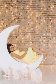 Adorable pregnant woman in yellow dress lies on a moon before a wall