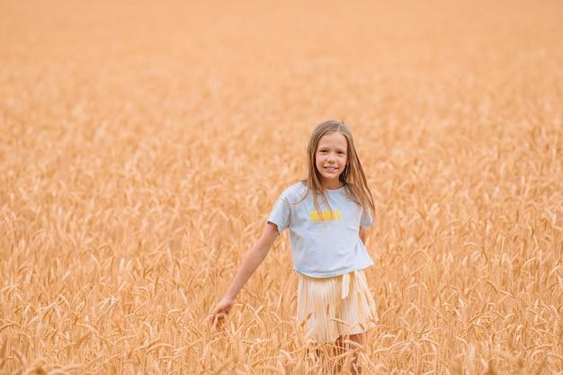 暖かく、日当たりの良い夏の日に麦畑を楽しく歩く愛らしい幼児女の子