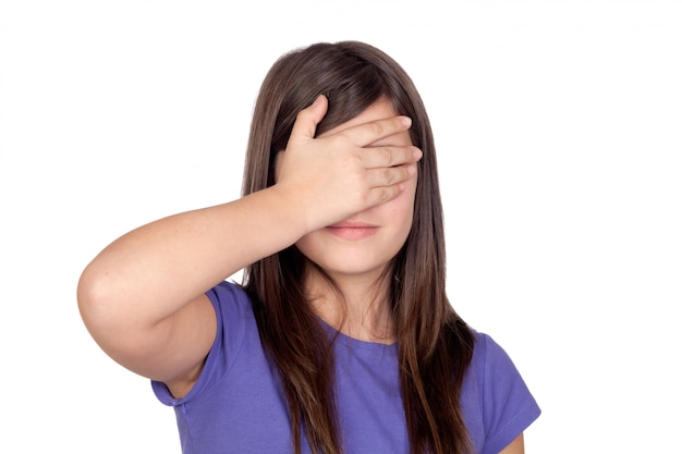 Adorable preteen covering her eyes on a white background