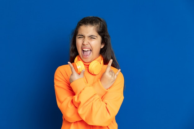 Adorable preteen girl with yellow jersey gesturing over blue wall