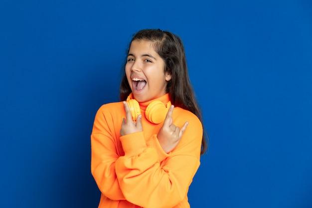 青い壁に身振りで示す黄色のジャージと愛らしいプレティーンの女の子