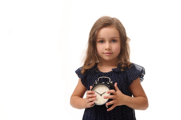 Adorable pretty 4 years old baby girl dressed in stylish dark blue evening attire, poses looking at the camera with an alarm clock in her hands, isolated against white background with copy space