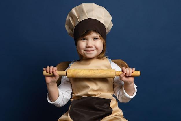 シェフの制服を着た愛らしいかわいい5歳の女の子が幸せそうに笑って、誕生日パーティーのためにクッキーを焼くのを手伝いに行き、スタジオでポーズをとり、両手で麺棒を持っています