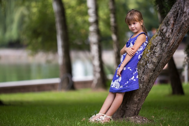 Adorable pretty young child girl with long blond hair in fashionable dress leaning on tree trunk.