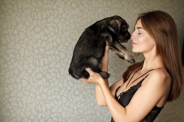 Adorable puppy of a pug on the hands of a beautiful woman