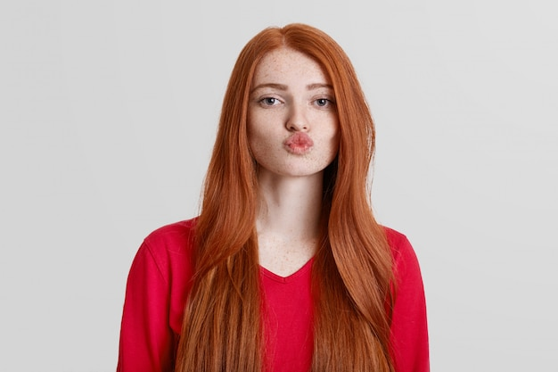 Adorable red haired female with freckled skin, rounds lips, going to kiss someone, has long redish hair, isolated on white. natural beautiful woman poses indoor. body language concept