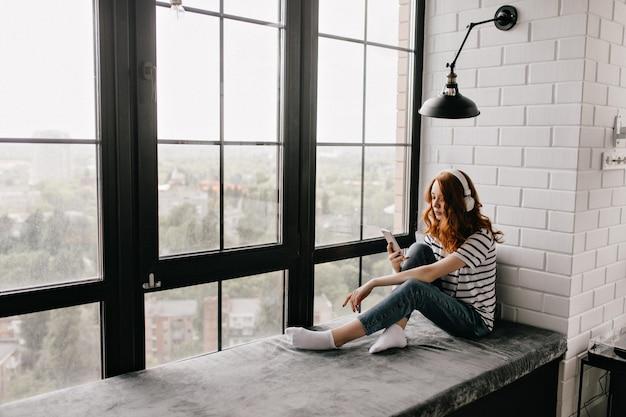 窓枠に座っているヘッドフォンで愛らしい赤毛の女の子。自宅で電話を使用して物思いにふける生姜の女性の屋内ショット。