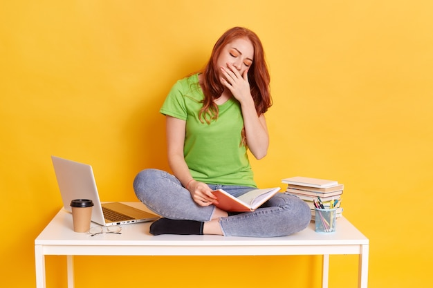 本とコンピューターを持って机の上に座っている愛らしい赤い髪の疲れた眠そうな女性
