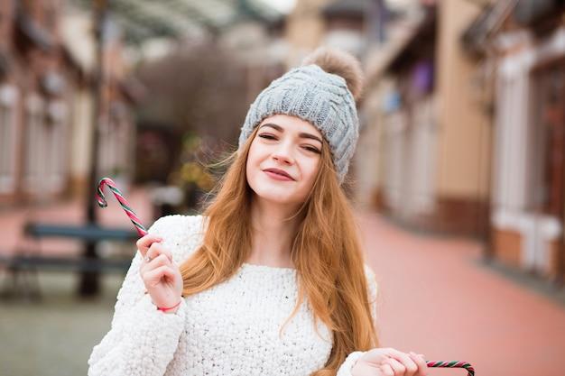 おいしいクリスマスのキャンディケインを保持している流行のアパレルで愛らしい赤い髪の若い女性