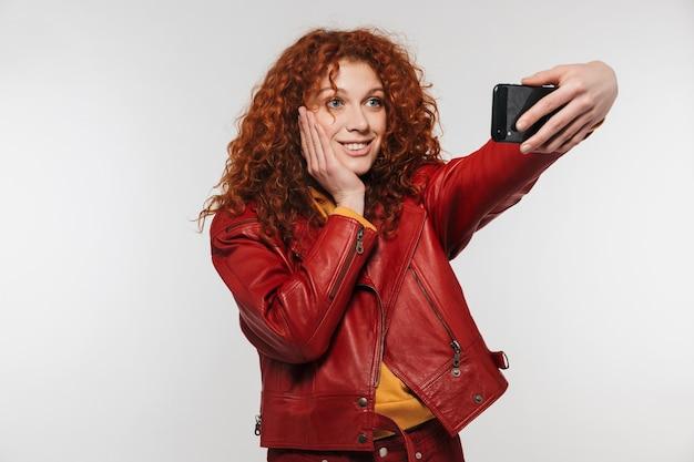Очаровательная рыжая женщина 20 лет в кожаной куртке улыбается и делает селфи на смартфоне, изолированном над белой стеной
