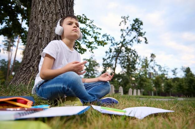 사랑스러운 학교 소년은 방과와 숙제를 마치고 지치고 피곤해하며 연꽃 자세로 앉아 머리에 무선 헤드폰을 얹고 명상합니다. 풀밭에 누워 있는 통합 문서 및 학용품