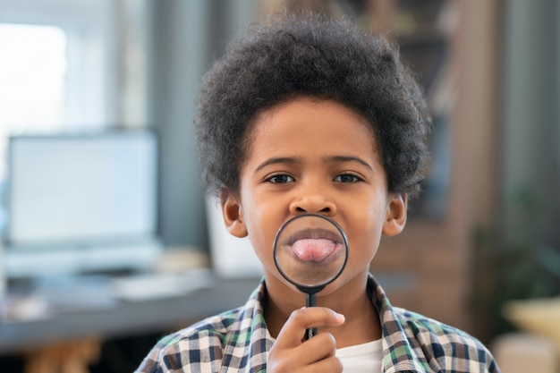 Adorable schoolboy of african ethnicity holding magnifying glass in front of his mouth and showing tongue while looking at you in domestic room
