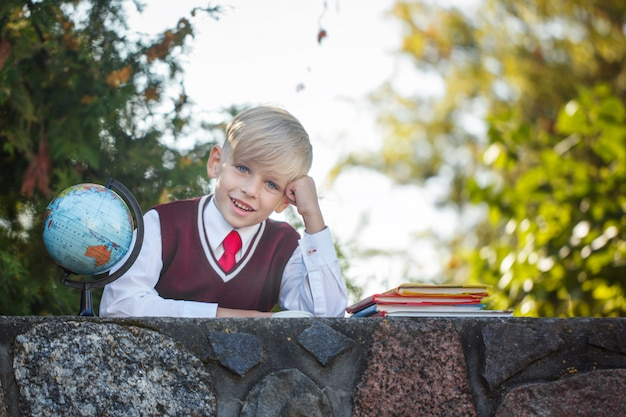 Adorable schoolboy with books and globe on outdoors. education for kids. back to school concept.