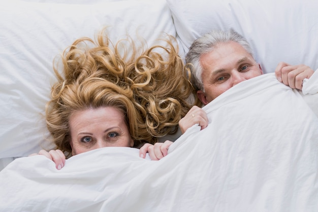 Adorable senior couple under bed sheets