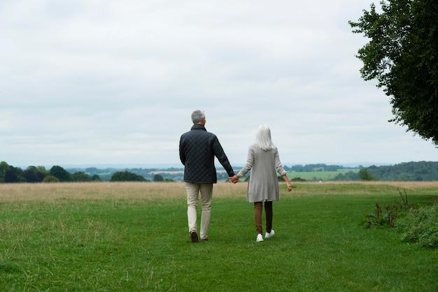散歩しながら愛情深い愛らしい老夫婦