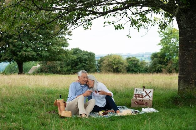 屋外でピクニックをしている愛らしい年配のカップル
