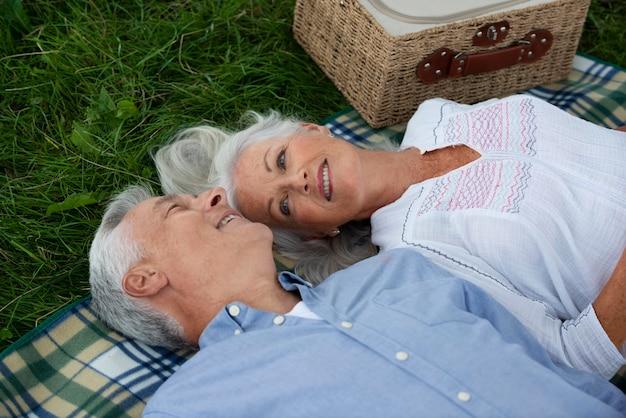 Adorable senior couple having a picnic outdoors