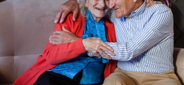 愛らしい年配の男性と女性を抱いて