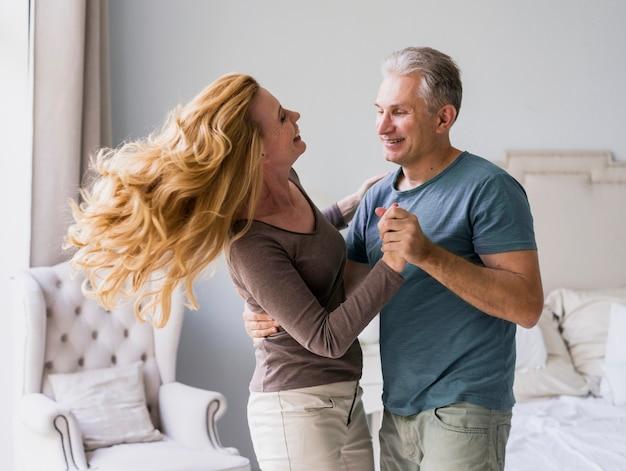 Adorable senior man and woman dancing together