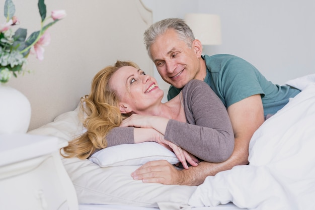 Adorable senior man and woman together in bed