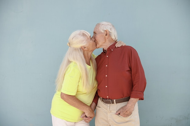 恋人の愛らしいシニアペアは、明るい灰色の背景にキスします