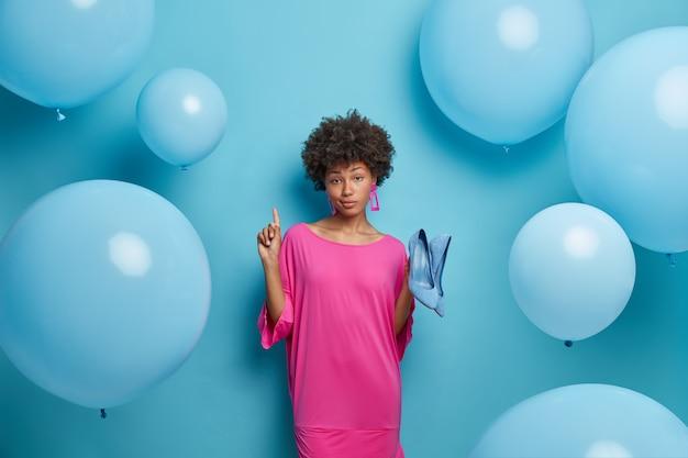 Adorabile donna dalla pelle scura seria pronta per la data imminente, indica sopra e mostra il negozio dove ha comprato scarpe, indossa abiti alla moda, sta contro il muro blu, palloncini gonfiati