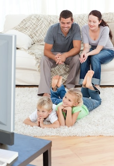 Adorable siblings watching television with their parents lying on the floor