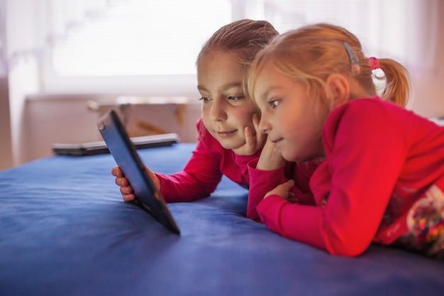 Очаровательные сестры смотрят видео на кровати