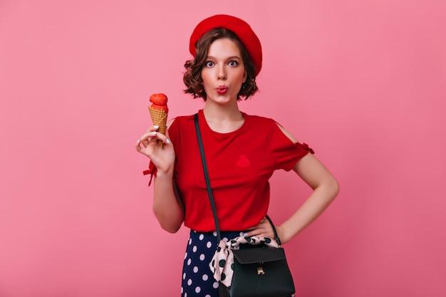 아이스크림을 먹는 빨간 블라우스에 사랑스러운 슬림 소녀. 짧은 머리 포즈와 화려한 백인 여자의 실내 샷.