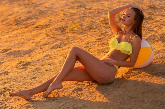 Adorable slim lady in swimsuit with beach ball in the sea at warm sunset