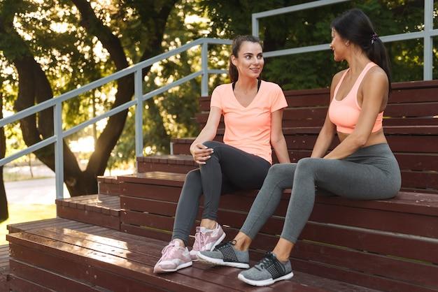 Очаровательные стройные женщины в спортивной одежде сидят и разговаривают на скамейке на спортивной площадке