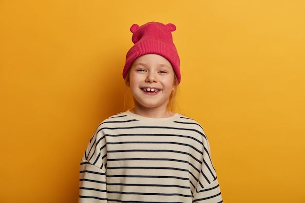 Adorable small child giggles positively has missing teeth, feels merry, rejoices nice day, wears pink fashionable hat and striped loose sweater, poses against yellow wall, makes memorable photo