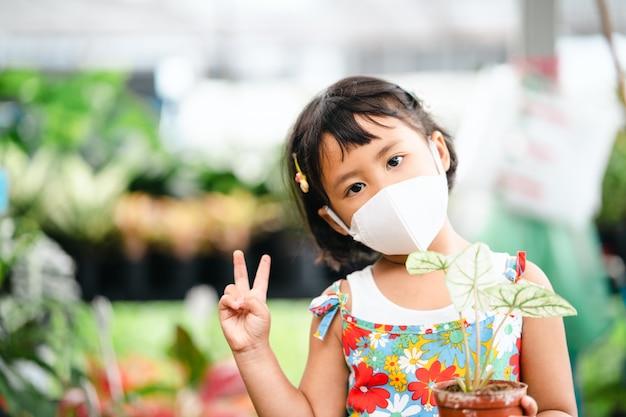 屋内で植木鉢を保持している保護フェイスマスクを身に着けている愛らしい小さな女の子