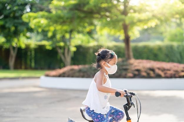 公園で自転車に乗って保護フェイスマスクを身に着けている愛らしい小さな女の子