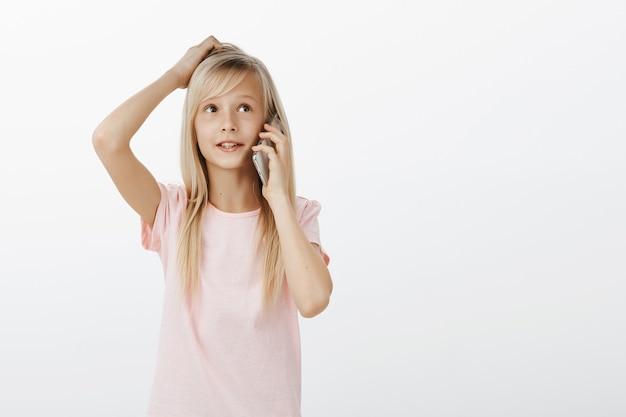 ブロンドの髪、スマートフォンで話して、頭をかいて、よそ見で愛らしいスマート女性の子供