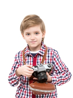 Adorable smart photographer kid holding black camera in hands looking