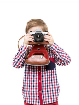 Adorable smart photographer kid holding black camera in hands