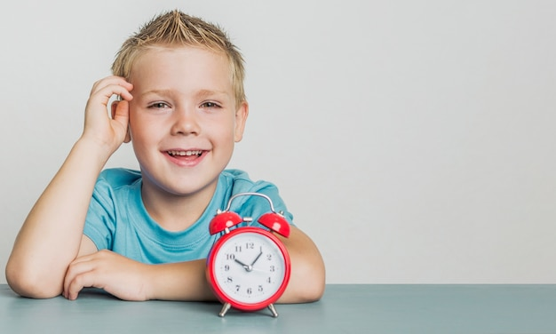 Adorable smiley young boy with a clock