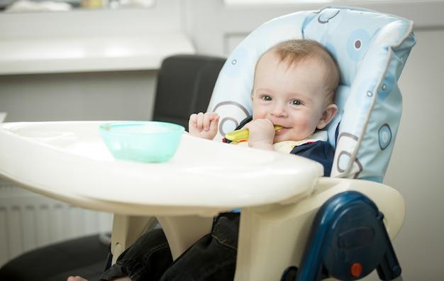 Очаровательный улыбающийся мальчик ест кашу ложкой