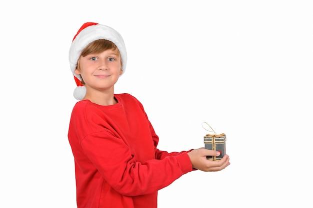 Очаровательный улыбающийся белокурый мальчик в красной шляпе и красном пуловере рождества или санта-клауса в ожидании нового
